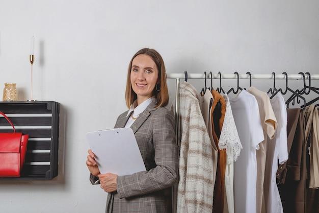 Стилист женщина с планшетом рядом с одеждой на стильных перилах в гардеробной