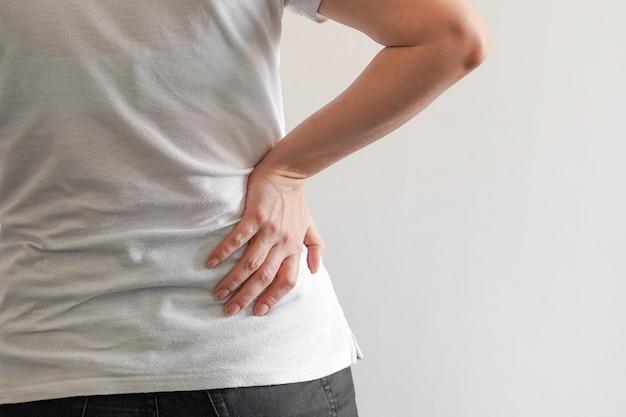 女性は腰痛に苦しんでいます。痛みで腰痛を抱えている女性の手。ヘルスケアの概念。