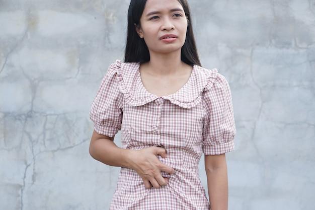 Женщина страдает от боли в животе, хронического гастрита, вздутие живота.