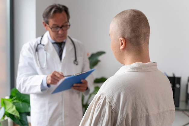 Woman suffering of breast cancer talking with her doctor