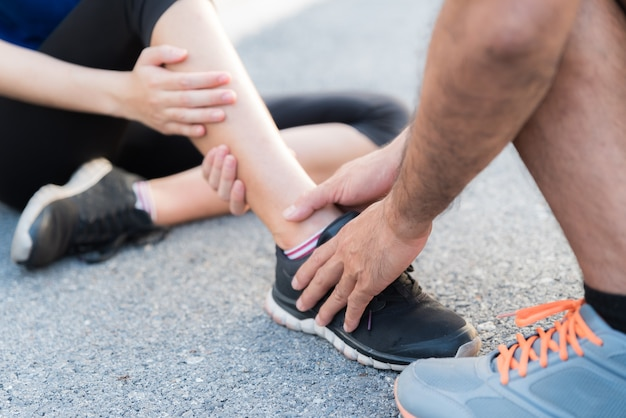 Woman suffering from an ankle injury while exercising, healthcare and sport concept.