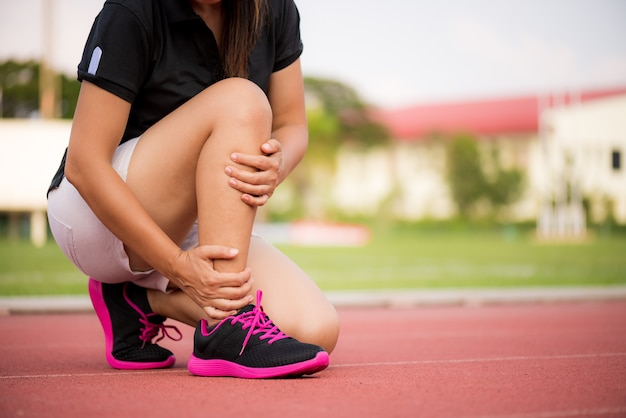 Woman suffering from an ankle injury while exercising on running track.