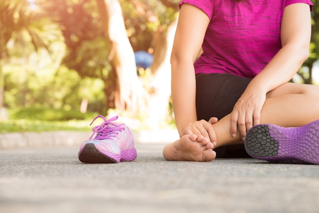 Woman suffering from an ankle injury while exercising.
