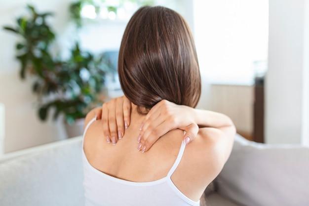 Женщина, страдающая от боли в спине, сидит дома на диване и трогает ее спину