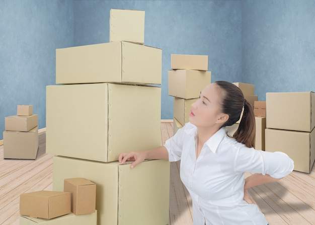 Woman suffering from backache while moving boxes