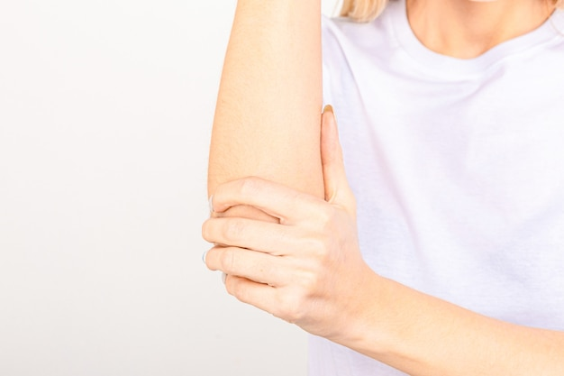 Женщина страдает хроническим ревматизмом суставов. боль в локте и концепция лечения.