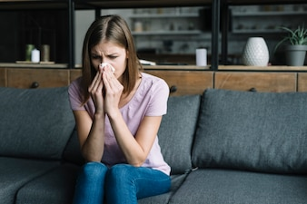 Woman suffering from cold blowing nose with tissue paper