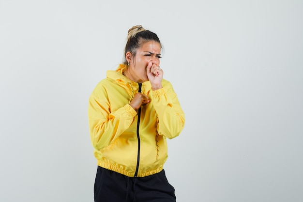 Woman suffering from cough in sport suit and looking sick. front view.