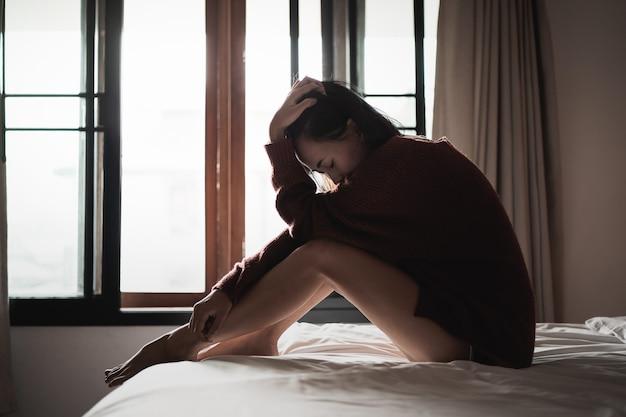 침실에서 침대에 앉아 우울증으로 고통받는 여성