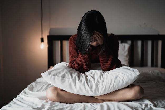 寝室のベッドに座ってうつ病に苦しんでいる女性