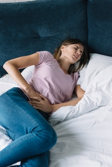 Woman suffering from diarrhoea lying on bed