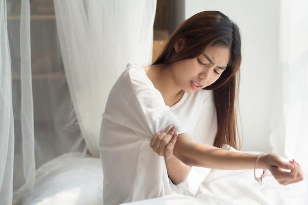 Женщина страдает от боли в локтевом суставе