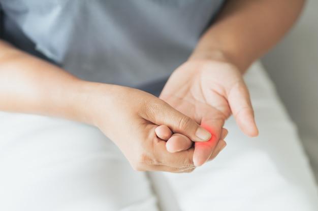 Женщина страдает от боли в суставах рук и пальцев с ревматоидным артритом с красной подсветкой
