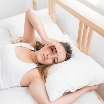 Woman suffering from headache lying on bed