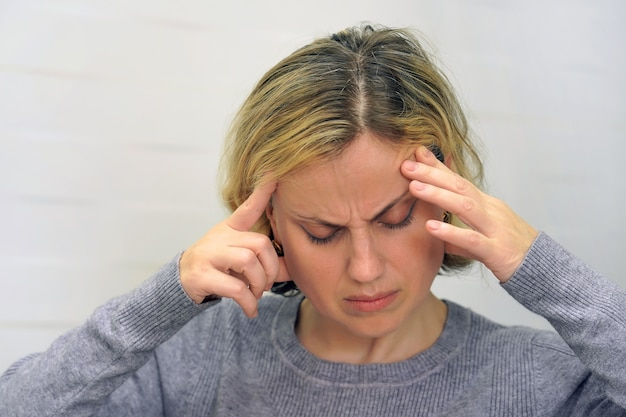 Woman suffering from headache migraine pain. girl squeezes her head.