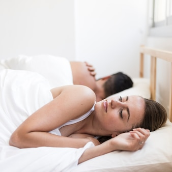 Woman suffering from insomnia lying on bed near her husband
