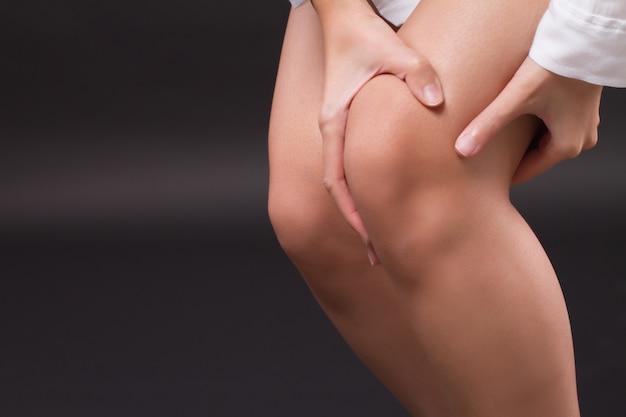 Женщина страдает от боли в коленном суставе, артрита, подагры