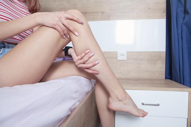 집에서 다리 통증으로 고통받는 여성.