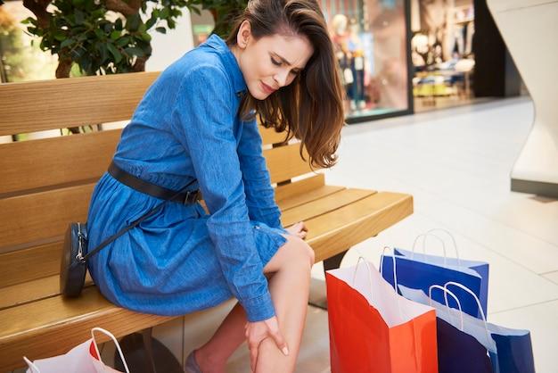 Женщина страдает от боли в ноге во время покупок