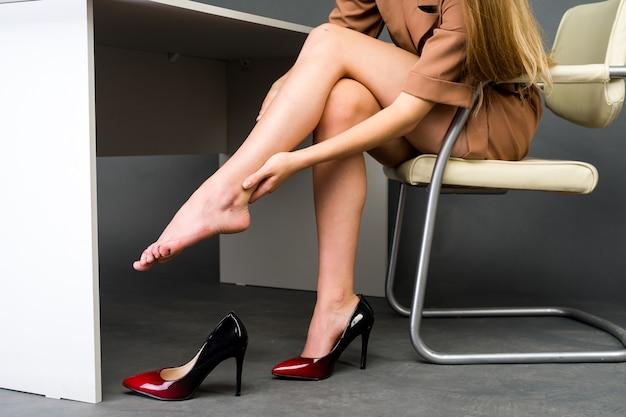 사무실에서 다리 통증으로 고통받는 여자. 그녀는 불편한 하이힐에서 끔찍한 굳은 살을 문질러