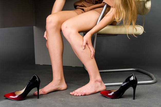 Женщина страдает от боли в ноге в офисе. она натирала ужасные мозоли от неудобных туфель на высоких каблуках
