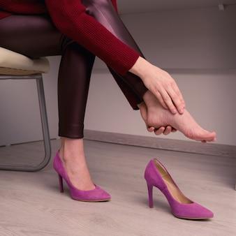 Женщина страдает от боли в ноге в офисе. натерла ужасные мозоли от неудобных туфель на высоких каблуках.