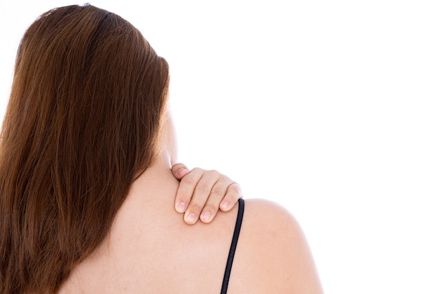 목과 어깨 통증으로 고통받는 여자는 흰 벽에 고립.