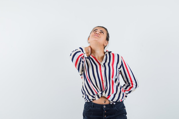 Женщина страдает от боли в шее в рубашке, юбке и выглядит истощенной.