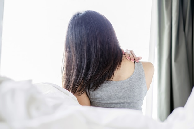 Woman suffering from neck and shoulder pain on bed