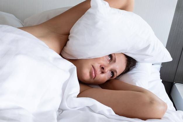 시끄러운 이웃으로 고통받는 여성이 베개로 머리를 가리고 있습니다. 스트레스와 나쁜 수면 개념