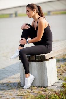 운동 후 다리에 통증에서 고통받는 여자