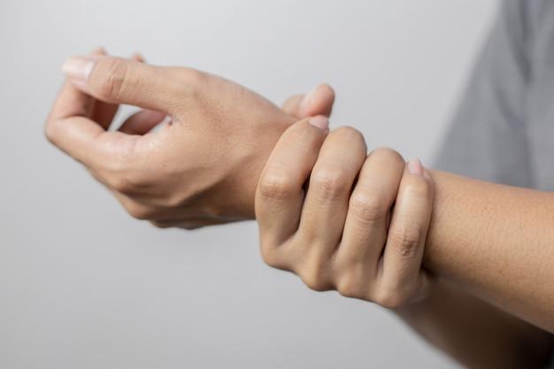 손목 통증으로 고통받는 여성. 여성 손목에 통증이 있습니다. 젊은여자가 그녀의 고통스러운 손목을 잡고