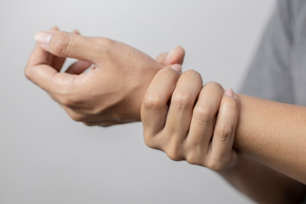 Woman suffering from pain in wrist. pain in a women wrist. young woman holding her painful wrist