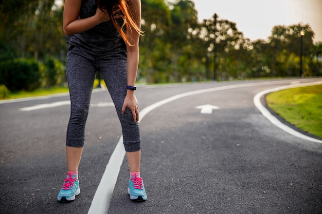 Woman suffering from painful chest or symptoms of heart disease while running in the park.