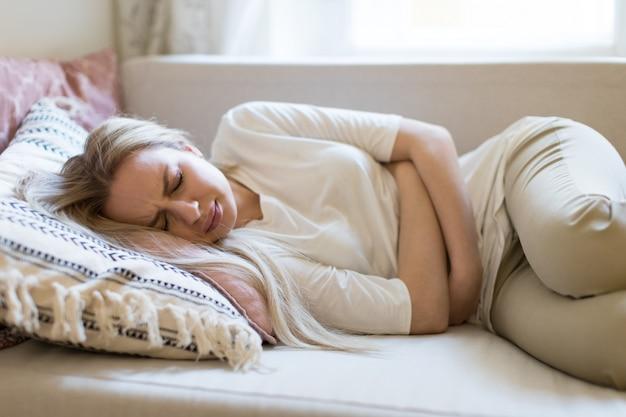 Женщина, страдающая от болей в животе, ощущая боль или спазмы в животе, лежа на диване. период менструации