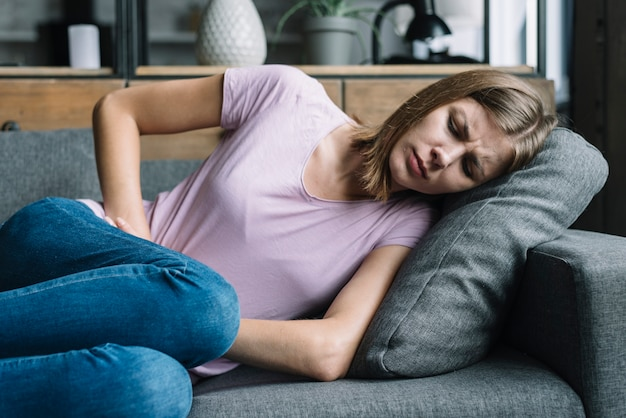Woman suffering from stomach pain lying on sofa