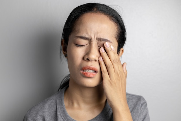 Woman suffering from strong eye pain.