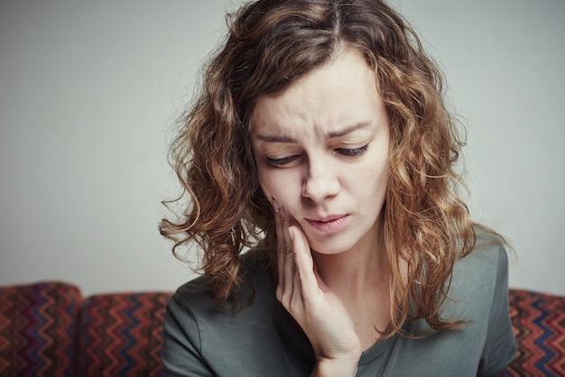 歯痛に苦しんでいる女性。歯の痛みの概念