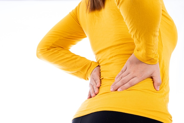 Woman suffering from waist and back pain isolated white.