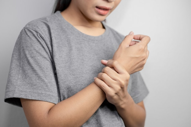 Женщина страдает от боли в запястье