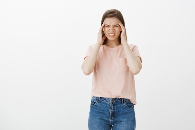Женщина страдает от сильной головной боли, трогает виски и гримасничает от болезненной мигрени