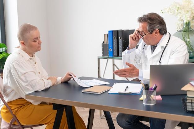 Женщина, страдающая от рака груди, разговаривает со своим врачом