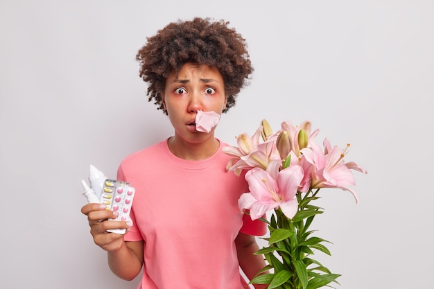 Woman suffers from allergic rhinitis has napkin stuck in nostril holds medicine has allergy to lilies looks embarrassed has swollen eyes isolated on white studio wall