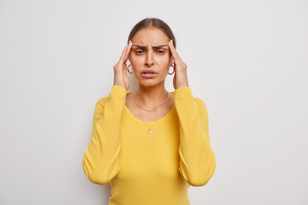 Woman suffers from headache keeps hands on temples frustrated of failure grimaces from painful ache needs painkillers wears casual yellow jumper on white
