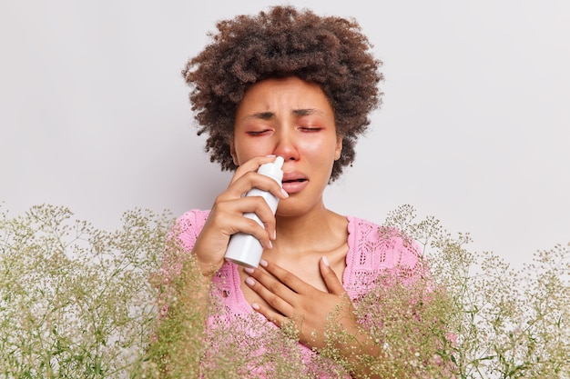 La donna soffre di naso che cola usa spray nasale ha occhi gonfi rossi ha una reazione allergica alla rinite su pose di piante selvatiche su bianco