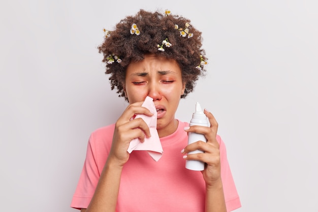 La donna soffre di allergia stagionale soffia il naso nel tovagliolo usa l'aerosol ha problemi di salute gli occhi rossi reagiscono all'allergene isolato su bianco