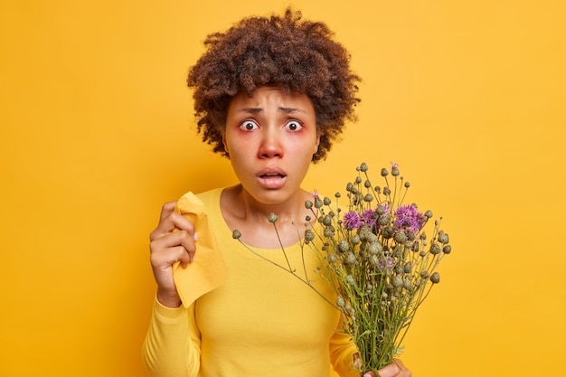 Woman suffers from seasonal allergy holds napkin bouquet of wildflowers has red itchy eyes as reaction on allergen poses on vivid yellow