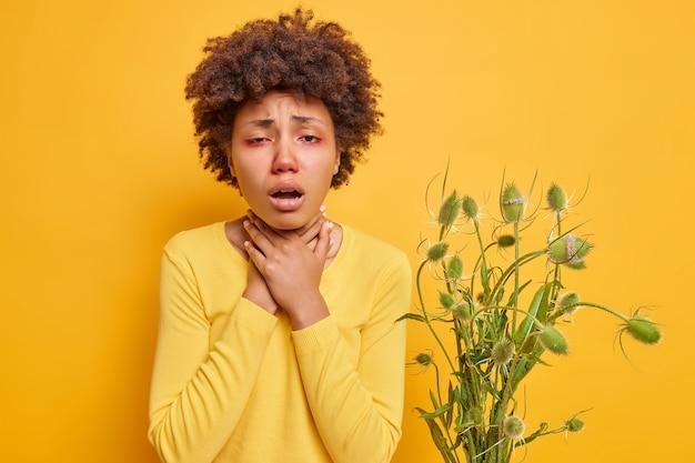 女性は窒息に苦しんでいる首に手を保ちますトリガーに反応します赤い目は黄色で隔離されたカジュアルなジャンパーを着て不健康に感じます