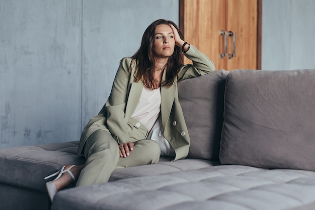 Woman in the suit sits on the couch thoughtfully.