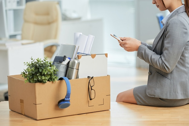 Woman in suit sitting on desk in office with belongings in box and using smartphone